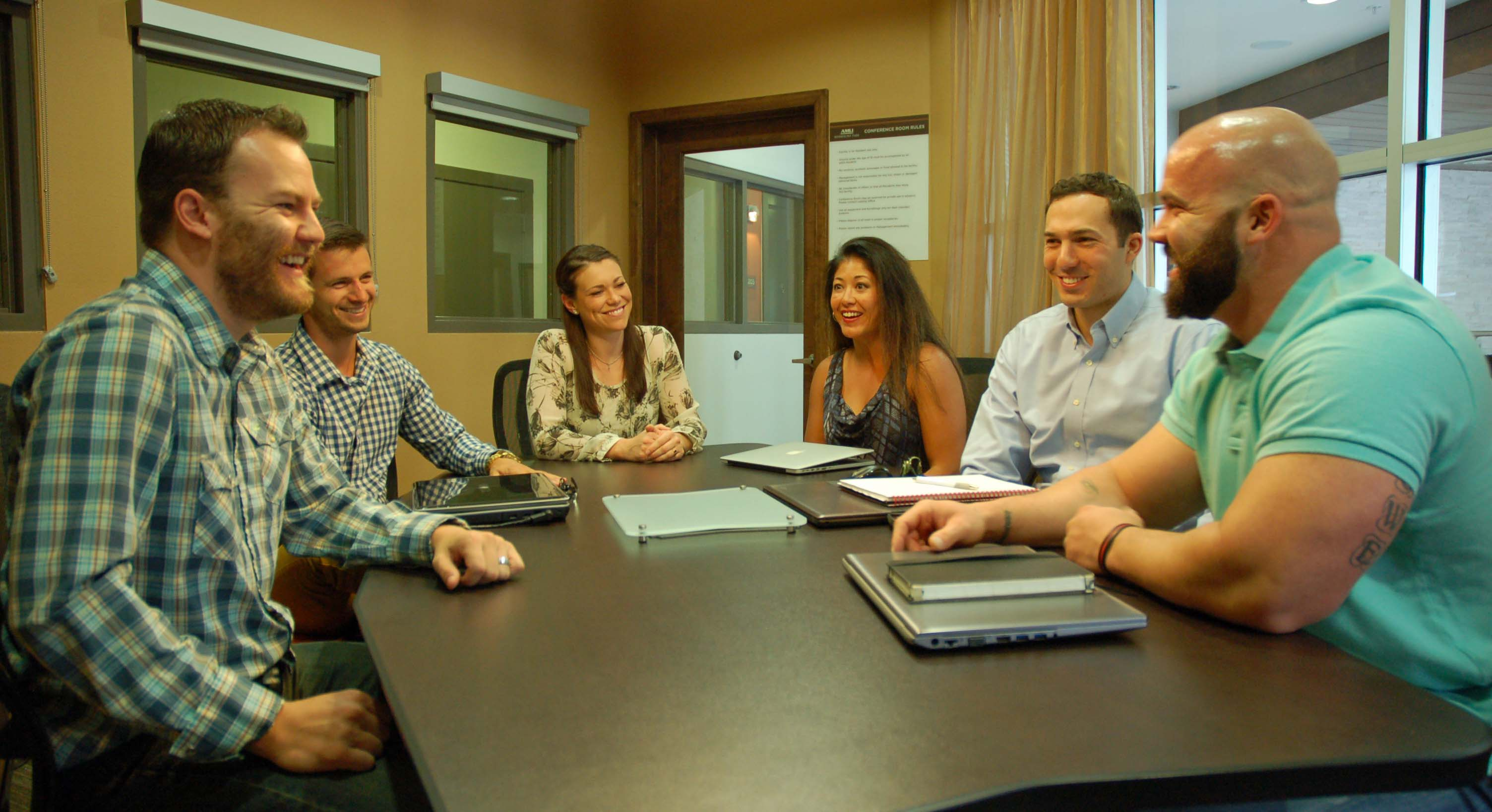 Matt (far right) and Amy Lowe (center left) start the day with their Denver-based business team.
