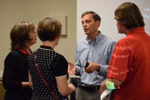 Tom Virden (center), the founder of Nymbl Science, speaks with attendees after the panel.